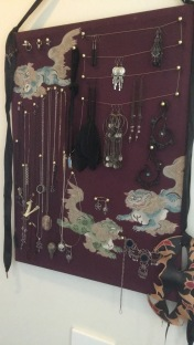 A photo of the jewellery board. A cork board I've covered in a purple scrap of fabric and have necklaces and earrings hanging off.