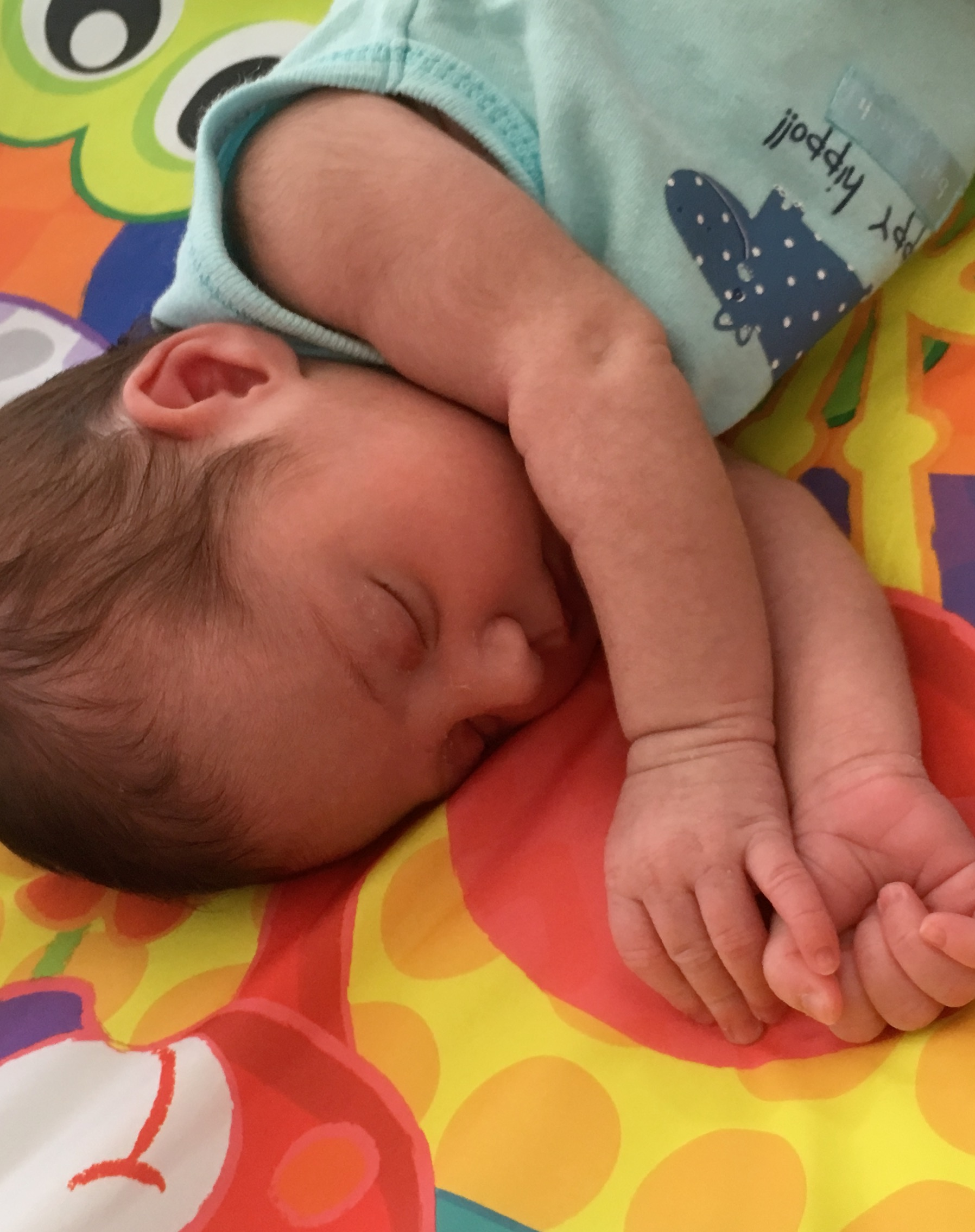 Photo of my 3 week old daughter, nicknamed Rabbit, sleeping on a colourful play mat.