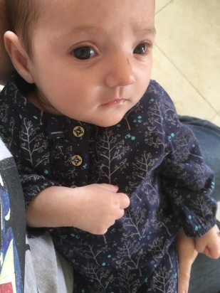 Photo of baby girl in a blue onsie with little grey trees on it.