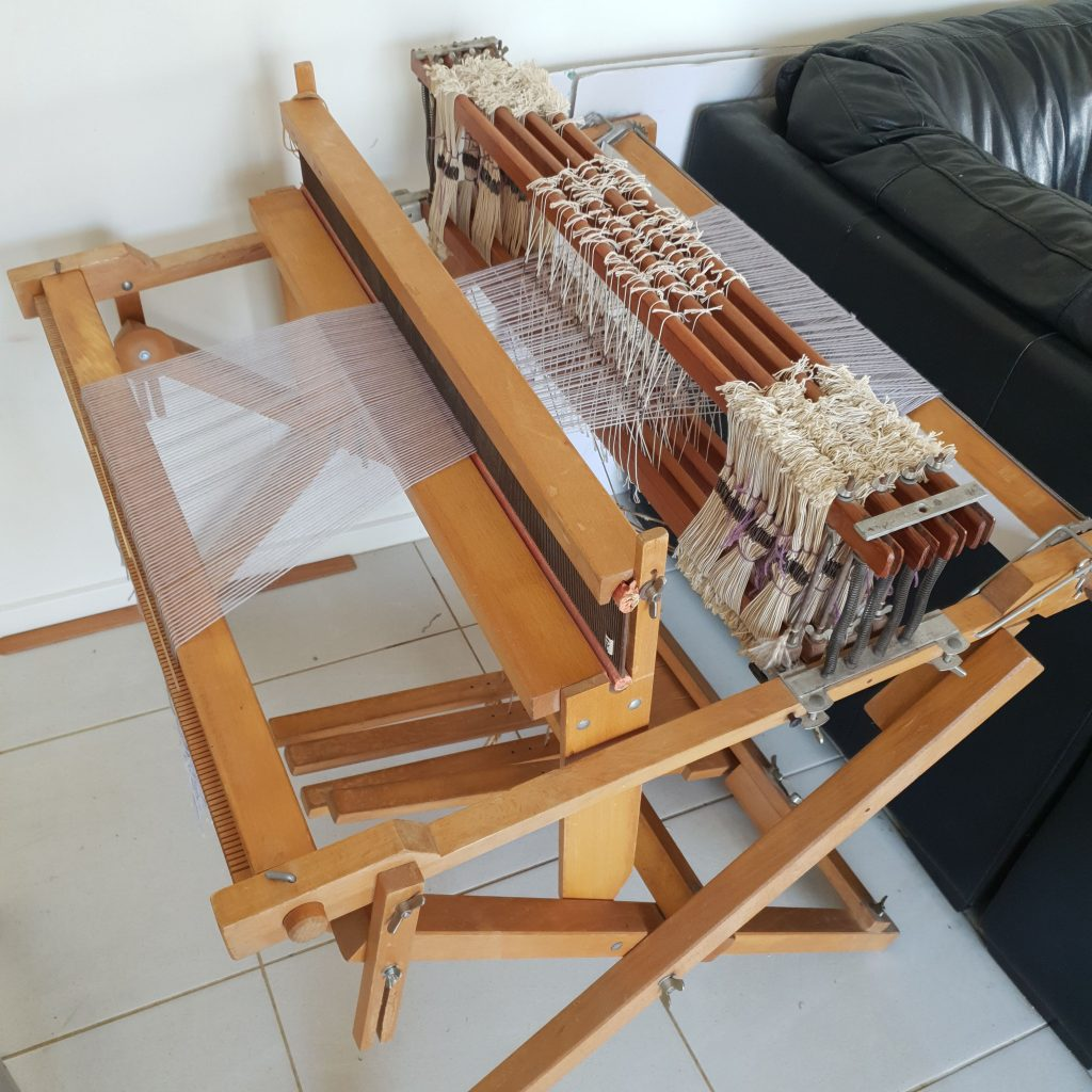 Image of a large floor loom with 4 shafts fully threaded with soft grey thread.